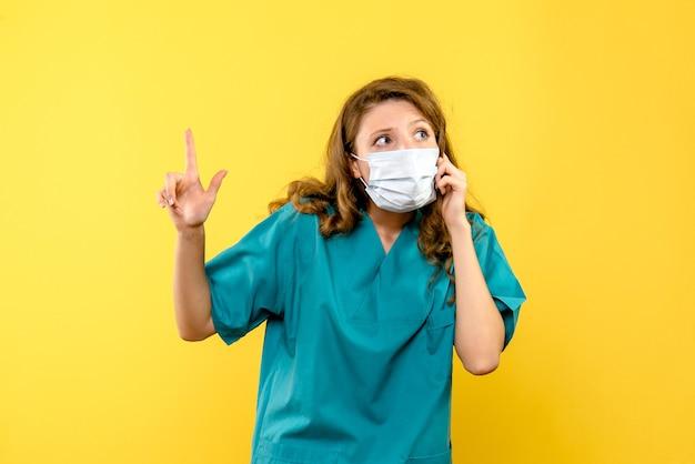 Vooraanzicht van vrouwelijke arts in masker op gele muur Gratis Foto