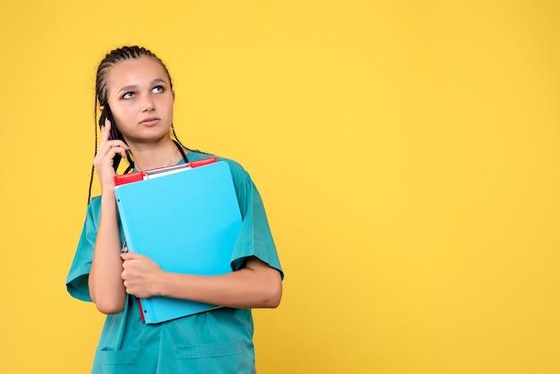 Vooraanzicht van vrouwelijke arts in medisch kostuum die op telefoon op gele muur spreken
