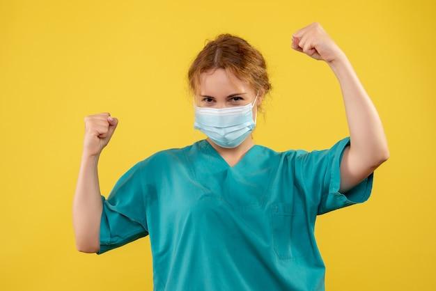 Vooraanzicht van vrouwelijke arts in medisch kostuum en masker die zich op gele muur verheugen