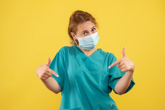 Vooraanzicht van vrouwelijke arts in medisch kostuum en masker op gele muur