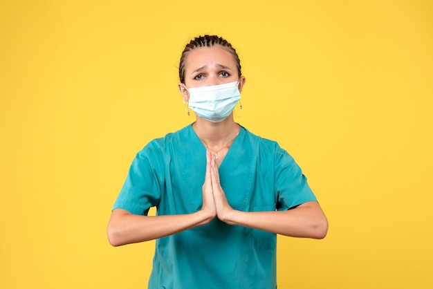 Vooraanzicht van vrouwelijke arts in medisch kostuum en steriel masker op gele muur