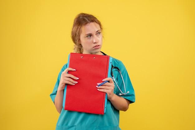 Vooraanzicht van vrouwelijke arts in medisch kostuum met documenten en analyse op gele muur