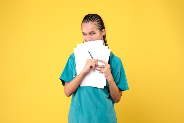 Vooraanzicht van vrouwelijke arts in medisch kostuum met documenten op gele muur