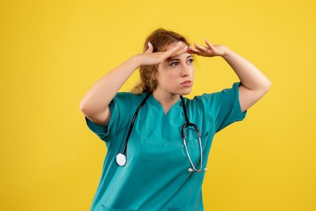 Vooraanzicht van vrouwelijke arts in medisch kostuum met stethoscoop op gele muur