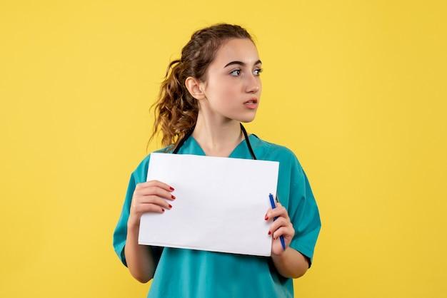 Vooraanzicht van vrouwelijke arts in medisch overhemd met documenten en stethoscoop op gele muur