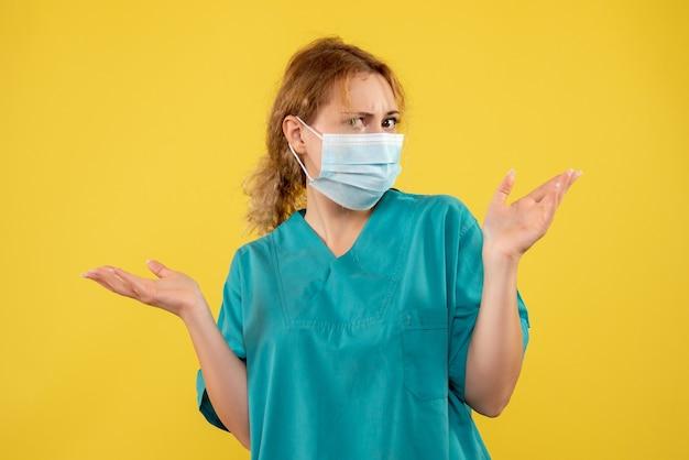 Vooraanzicht van vrouwelijke arts in steriel beschermend masker op gele muur