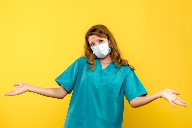 Vooraanzicht van vrouwelijke arts in steriel masker op gele muur