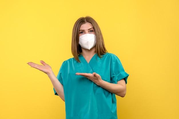 Vooraanzicht van vrouwelijke arts met beschermend masker op gele muur