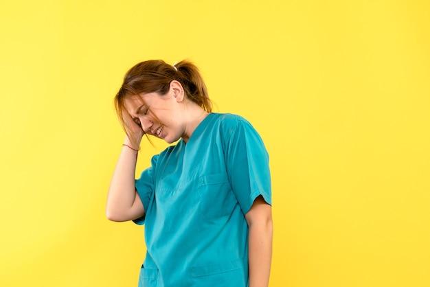 Vooraanzicht van vrouwelijke arts met hoofdpijn op gele muur