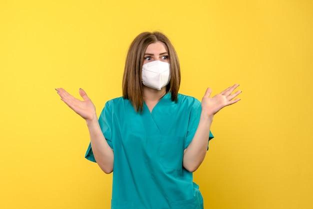 Vooraanzicht van vrouwelijke arts met masker op gele muur