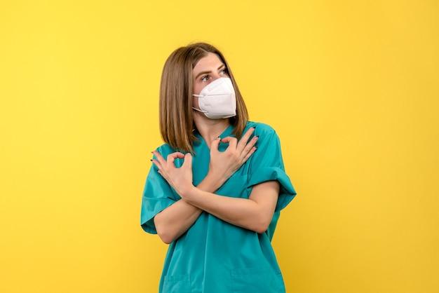 Vooraanzicht van vrouwelijke arts met masker op gele vloer pandemische emotie van het virusziekenhuis