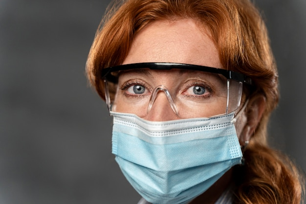 Vooraanzicht van vrouwelijke arts met medisch masker en veiligheidsbril