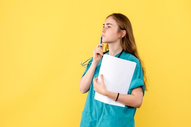 Vooraanzicht van vrouwelijke arts met medische papieren