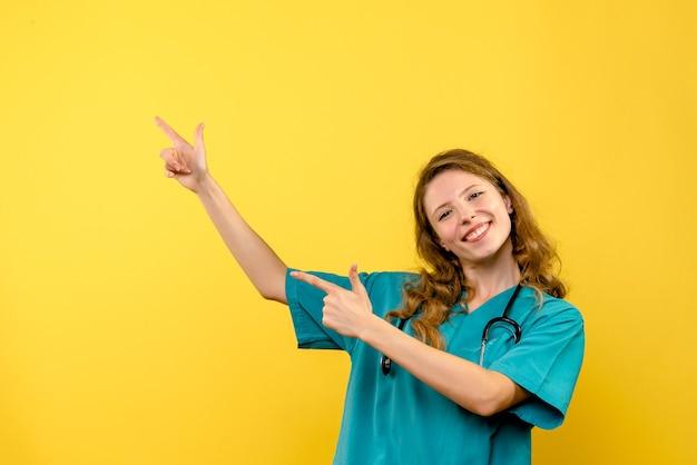 Vooraanzicht van vrouwelijke arts op gele muur