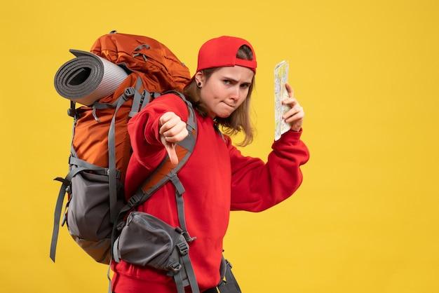 Vooraanzicht van vrouwelijke backpacker die reiskaart houdt die duim omlaag maakt