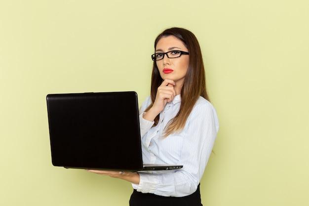 Vooraanzicht van vrouwelijke beambte in wit overhemd en zwarte rok die haar laptop op de lichtgroene muur met behulp van