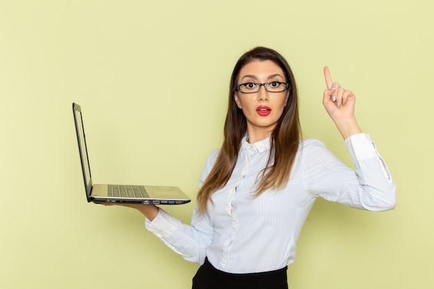 Vooraanzicht van vrouwelijke beambte in wit overhemd en zwarte rok die laptop op de lichtgroene muur houdt