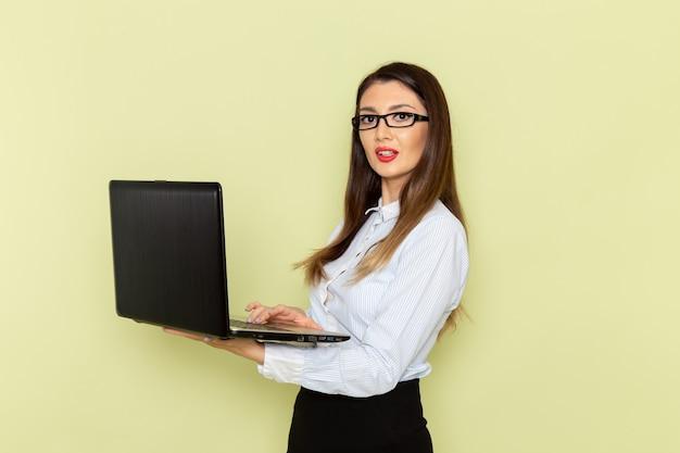 Vooraanzicht van vrouwelijke beambte in wit overhemd en zwarte rok met behulp van haar laptop op lichtgroen bureau kantoormedewerker drukke werkbaan