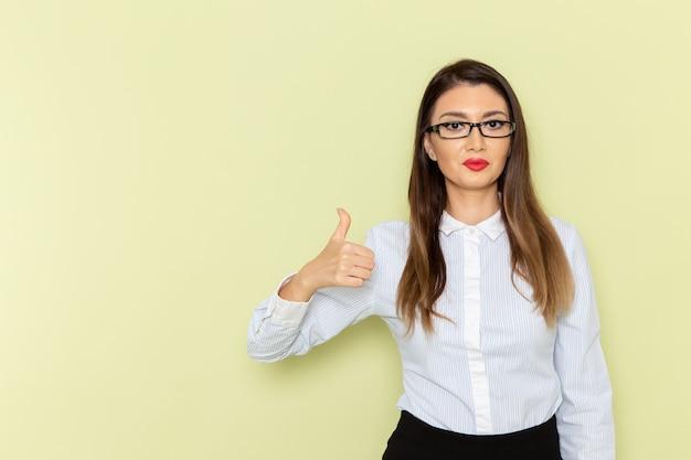 Vooraanzicht van vrouwelijke beambte in wit overhemd en zwarte rok op lichtgroene muur