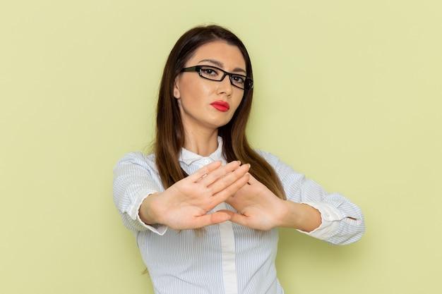 Vooraanzicht van vrouwelijke beambte in wit overhemd en zwarte rok poseren met voorzichtige uitdrukking op groene muur
