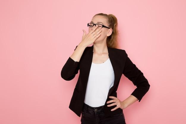 Vooraanzicht van vrouwelijke beambte in zwarte strikte jas geeuwen op roze muur