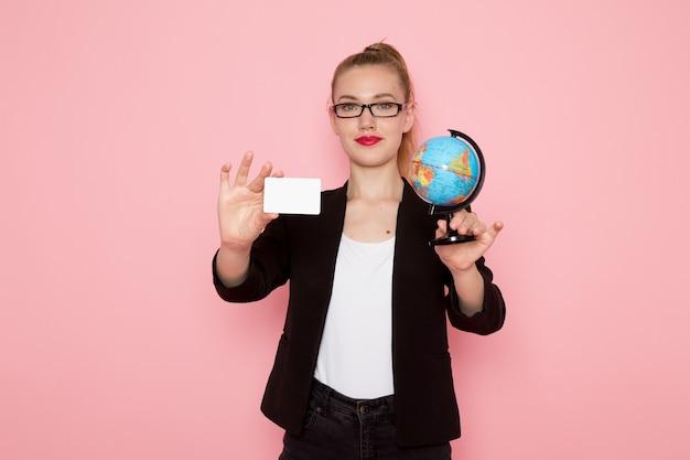 Vooraanzicht van vrouwelijke beambte in zwarte strikte jas glimlachend bedrijf globe en kaart op lichtroze muur