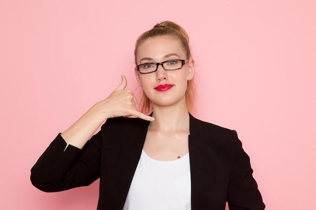 Vooraanzicht van vrouwelijke beambte in zwarte strikte jas lachend met telefoontje pose op roze muur