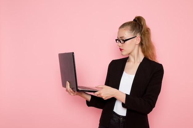 Vooraanzicht van vrouwelijke beambte in zwarte strikte jas met behulp van haar laptop op de roze muur