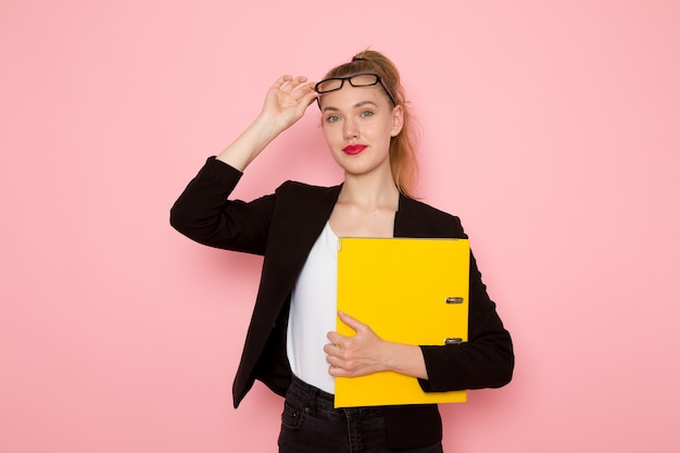 Vooraanzicht van vrouwelijke beambte in zwarte strikte jas met geel bestand op de lichtroze muur
