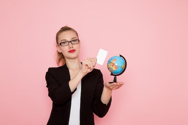 Vooraanzicht van vrouwelijke beambte in zwarte strikte jas met witte kaart en globe op lichtroze muur