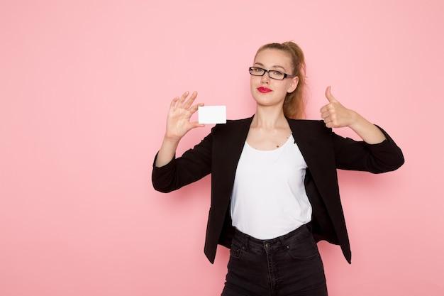 Vooraanzicht van vrouwelijke beambte in zwarte strikte jas met witte kaart lachend op lichtroze muur