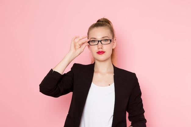 Vooraanzicht van vrouwelijke beambte in zwarte strikte jas poseren aan haar zonnebril op lichtroze muur te raken