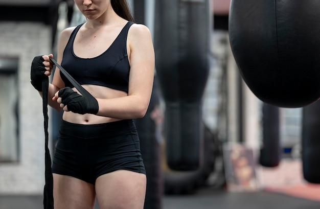 Vooraanzicht van vrouwelijke bokser die voor opleiding voorbereidingen treft