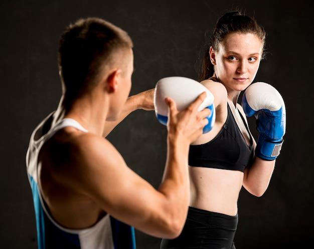 Vooraanzicht van vrouwelijke bokser en trainer