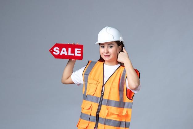 Vooraanzicht van vrouwelijke bouwer die rood verkoopbord houdt en op witte muur glimlacht