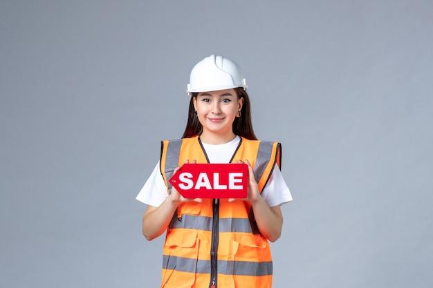 Vooraanzicht van vrouwelijke bouwer die rood verkoopbord op grijze muur houdt