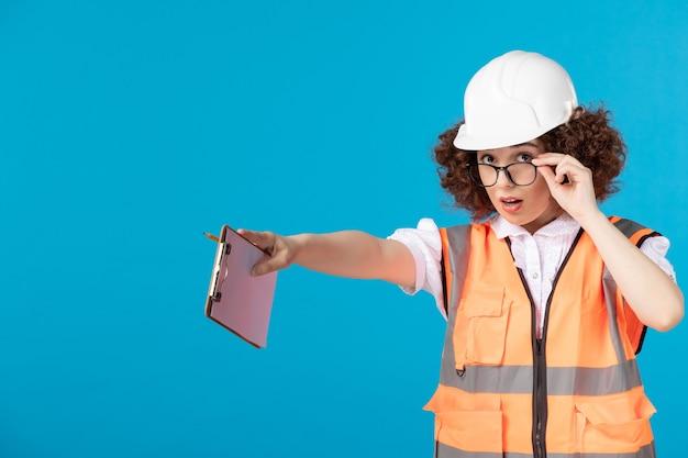 Vooraanzicht van vrouwelijke bouwer in uniform controlerend werk op blauwe muur