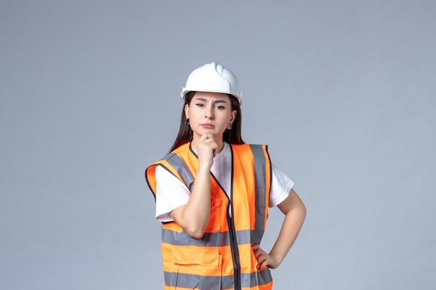 Vooraanzicht van vrouwelijke bouwer in uniform denken op witte muur