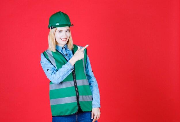 Vooraanzicht van vrouwelijke bouwer in uniform, helm en wijzende vinger in de rechterbovenhoek, met promo-aanbieding met blij gezicht