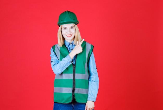 Vooraanzicht van vrouwelijke bouwer in uniform, helm naar rechts met wijsvinger en lachend met open mond