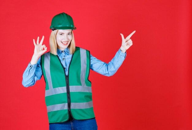 Vooraanzicht van vrouwelijke bouwer in uniform, helm naar rechts met wijsvinger en ok gebaar tonen