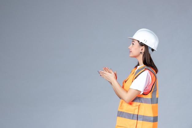 Vooraanzicht van vrouwelijke bouwer in uniform klappen op iets op grijze muur