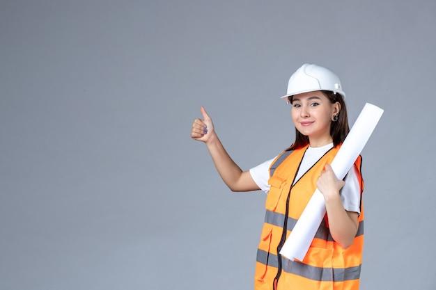 Vooraanzicht van vrouwelijke bouwer in uniform met poster in haar handen op grijze muur