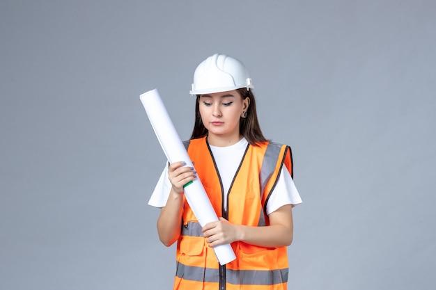 Vooraanzicht van vrouwelijke bouwer in uniform met poster in haar handen op witte muur