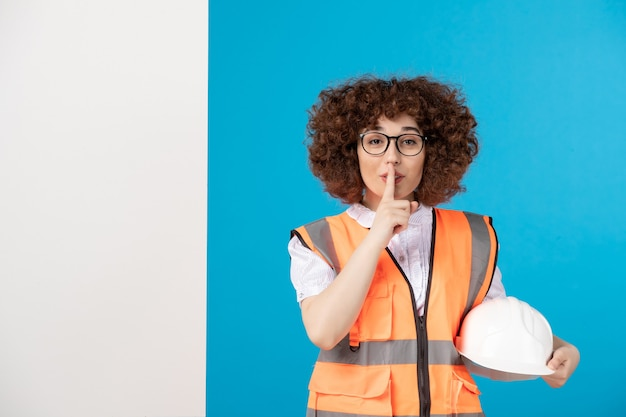 Vooraanzicht van vrouwelijke bouwer in uniform op de blauwe muur