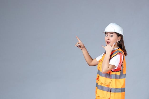 Vooraanzicht van vrouwelijke bouwer in uniform op witte muur