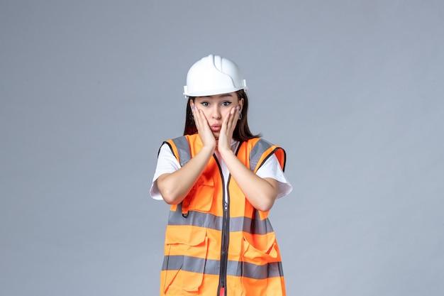 Vooraanzicht van vrouwelijke bouwer in uniform verrast op witte muur