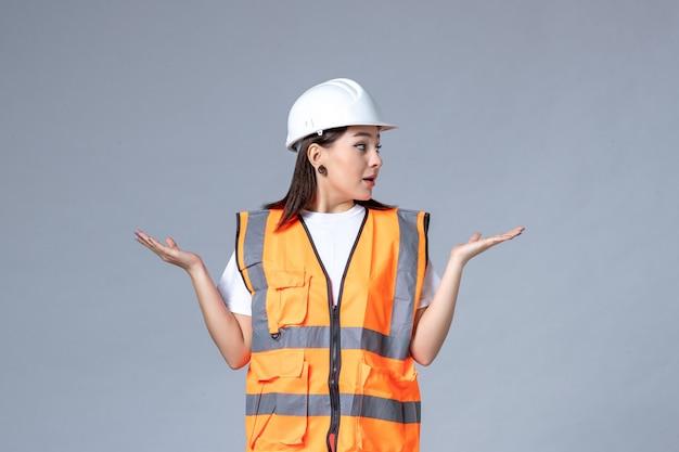 Vooraanzicht van vrouwelijke bouwer in uniforme en beschermende helm op grijze muur