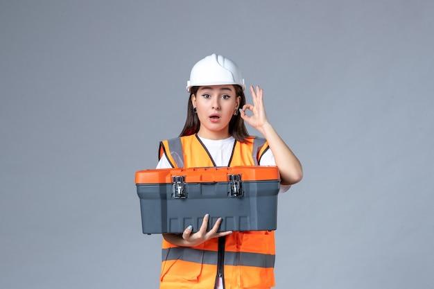 Vooraanzicht van vrouwelijke bouwer met gereedschapskoffer op grijze muur