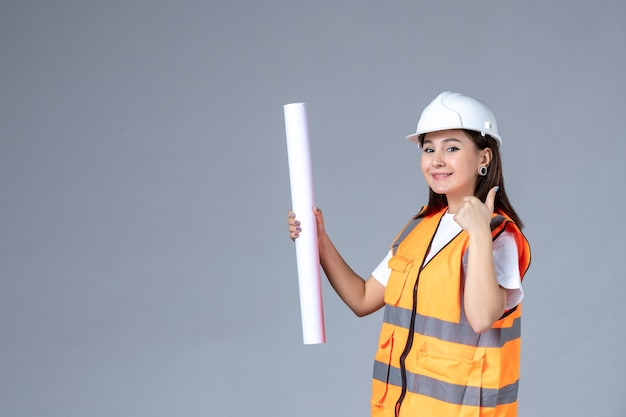 Vooraanzicht van vrouwelijke bouwer met poster in haar handen op grijze muur